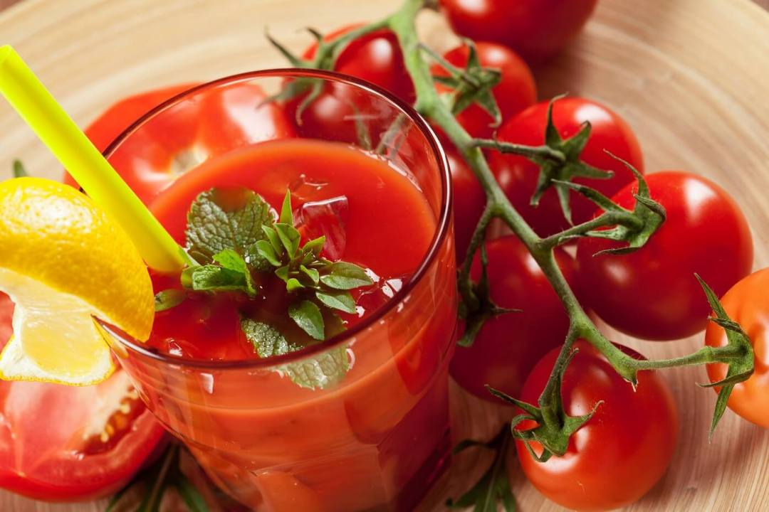 Tomato Juice with Quarter of lemon juice - Glass of tomato Juice with around it tomatoe