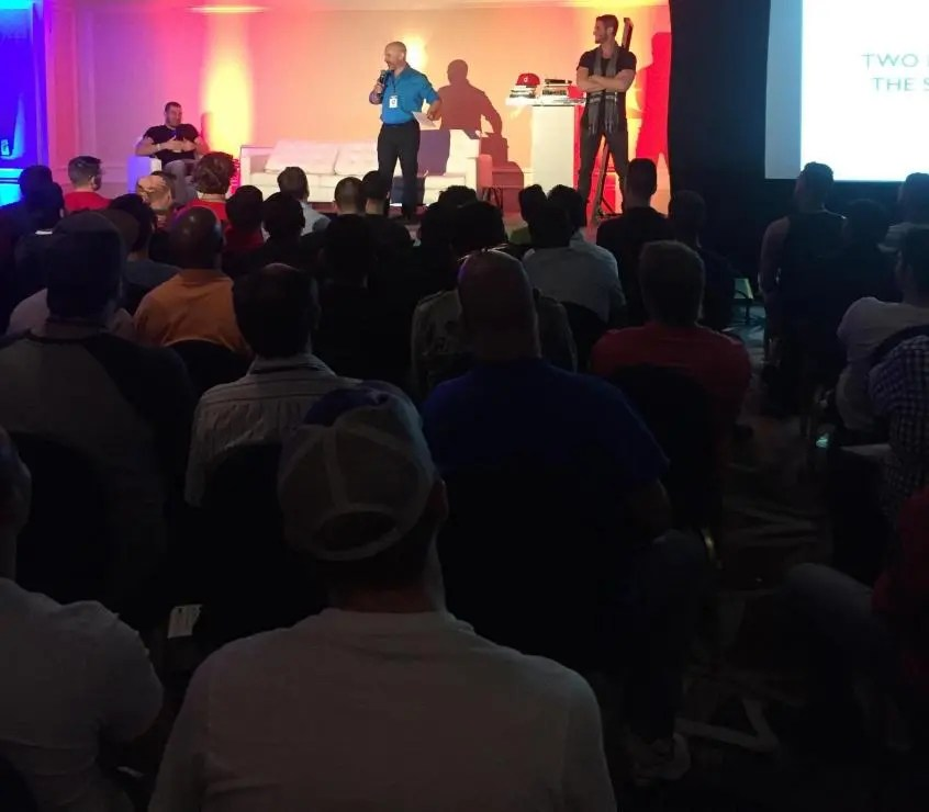 talking on stage in front of huge crowd of captivated men