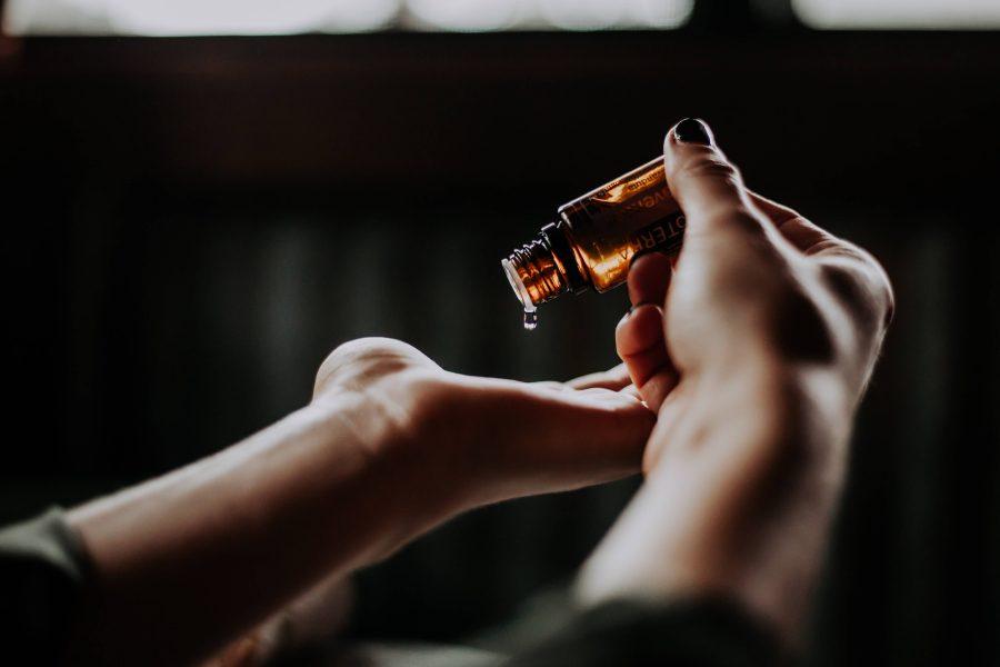 mains de femme verser huile essentielles goutte