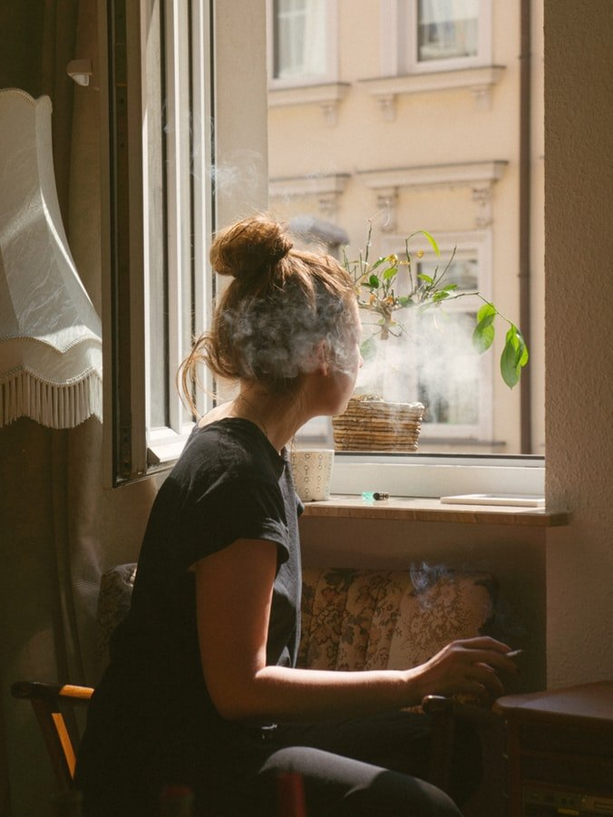 Woman smoking by window