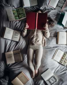Child on bed with books