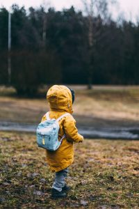 Little boy in raincoat and backpack