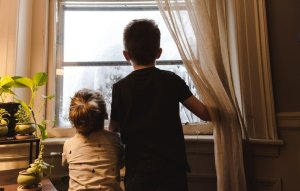 Children watch snow through window