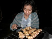 Euree tediously grills small chicken drums.