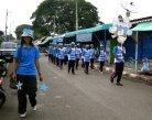 Blue teams parades down the street with their Thai teacher leader