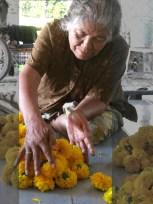 Yai helps Aunt Dan string flowers for merit making.