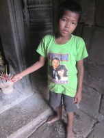 A Young Cambodian Boy Selling Incense in the Temple