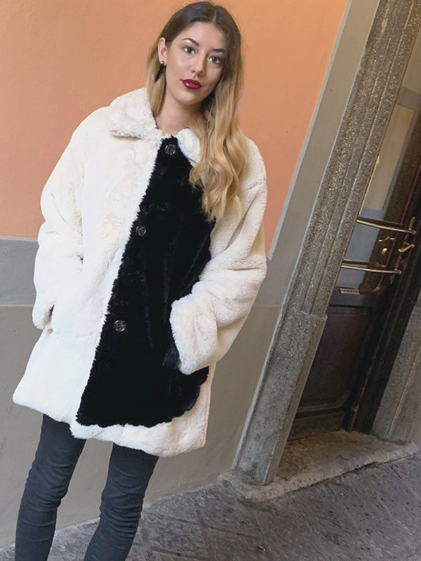 The Quarter Moon Faux Coat by Julia DiLorenzo is worn by a model with peach wall behind. Her faux fur coat is white on the left side and black on the right half, except for the right sleeve which is white.