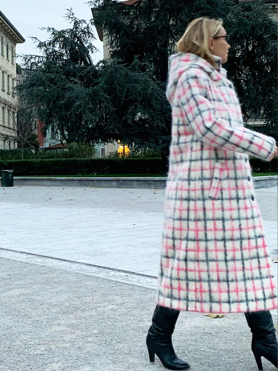 Woman walking on city street in a long white and pink plaid mohair coat and black heeled boots.