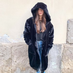 Woman leaning on stone wall wearing a faux fur cardi-coat from Julia Di Lorenzo. The coat has an oversized comfy hoodie and two large pockets with warm recycled down inside.