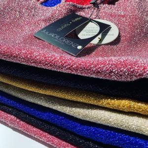 metallic shirts folded in pink, yellow, and blue by Julia Di Lorenzo. Slow fashion movement with ethical materials