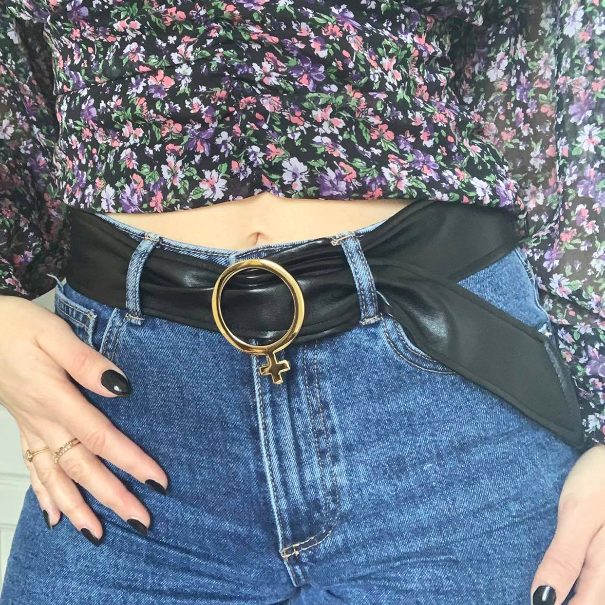 Black venus style belt with white gold buckle and black vinyl material in blue jeans and crop top on a model wearing black nail polish.