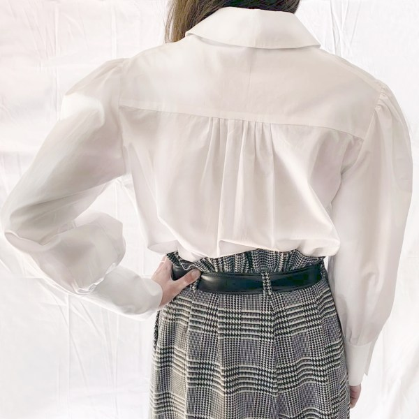 Back shot of white cotton blouse on a model also wearing jacquard shorts with black leather belt with white gold buckle. Model is wearing black lipstick and has her hand on her left hip.