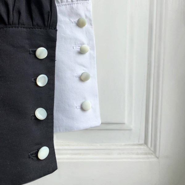 close-up image of the wrist cuffs on Julia Di Lorenzo white and black women's blouses. Made with 100% cotton fabric.