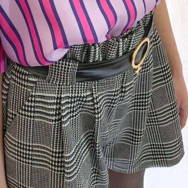 Model wearing jacquard shorts womens. Model is wearing a metallic neck tie and leather black belt with a white gold Venus belt buckle. Wearing a metallic blouse in lavender and pink vertical stripes.