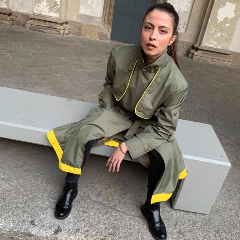 Model sits on bench in khaki raincoat trench-style with bright yellow bottom trim and accent color.