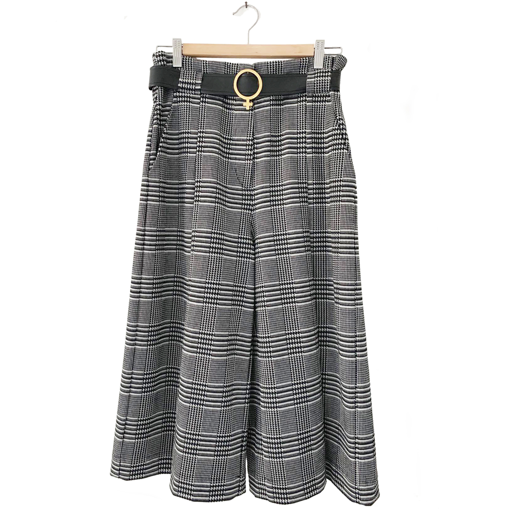 Women's culottes made with jacquard fabric black and white plaid style with buckle loops holding a Venus shaped black vinyl belt.