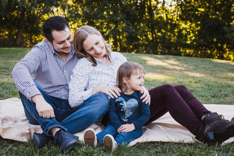 Family photo session. Parents with child sitting on a picnic blanket.