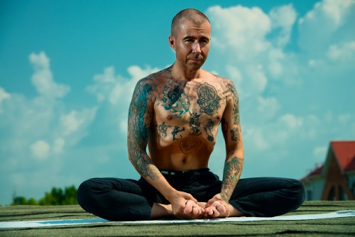 Tattooed bold man meditates in the lotus position sitting on a roof over blue sky