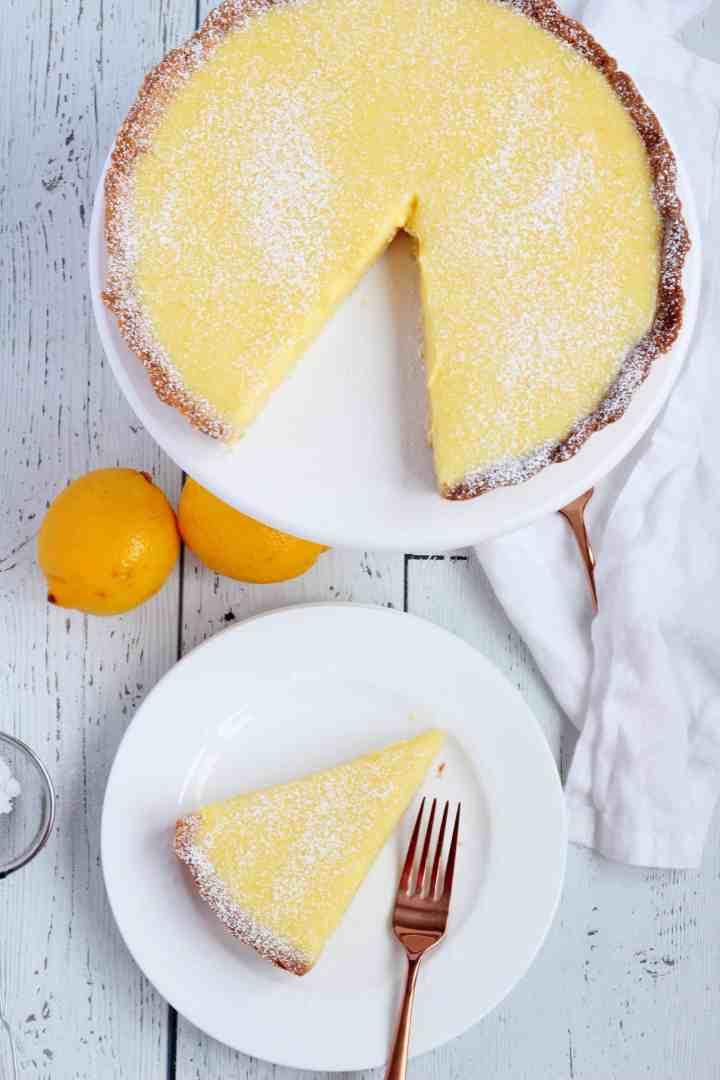 Lemon tart slice on white plate with whole tart on cake stand