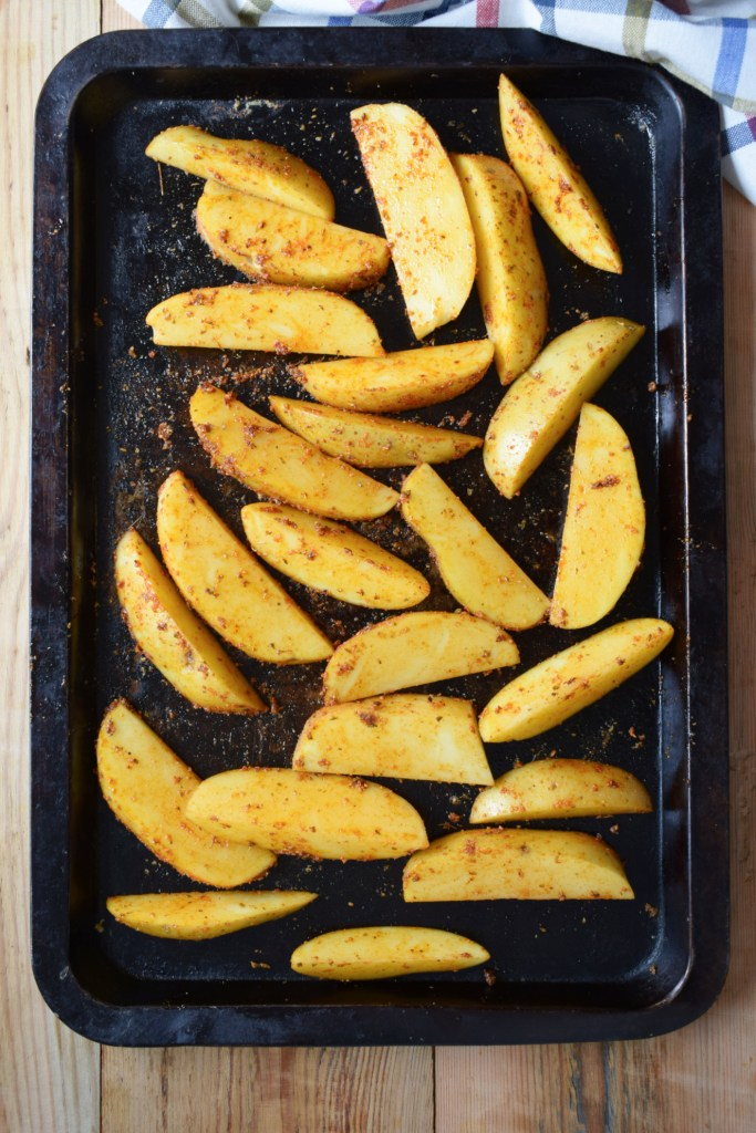 potatoes on a baking tray rubbed in a spice blend