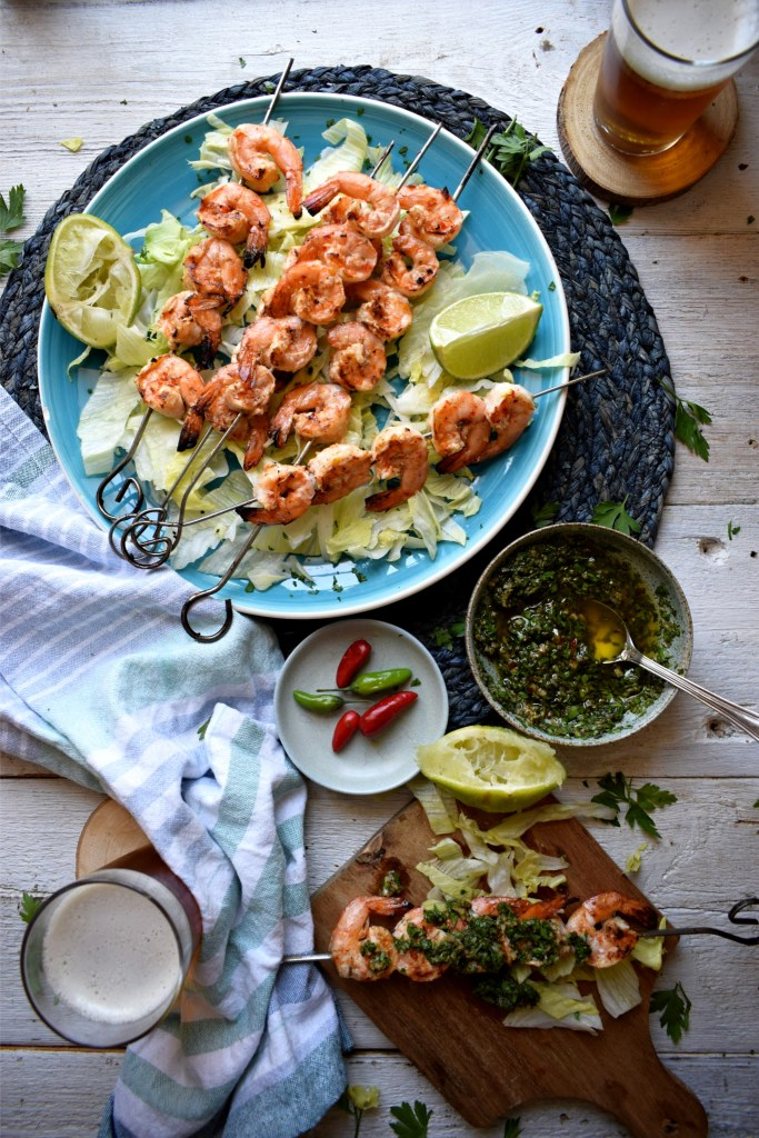 Table setting of grilled shrimp with chimichurri salsa and drinks