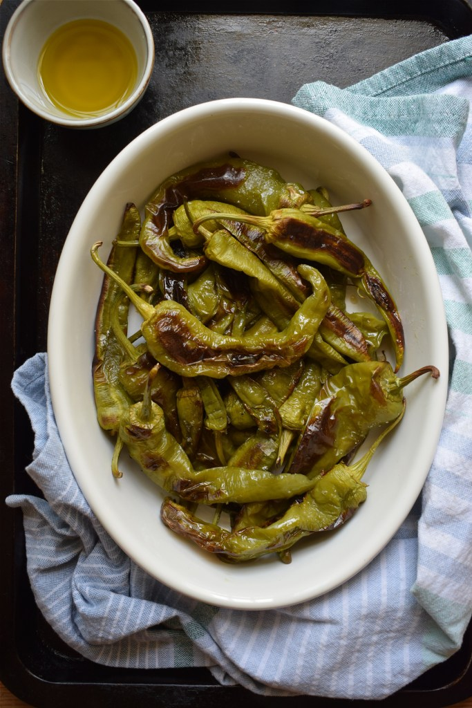 over head view of italian roasted green peppers on a baking sheet