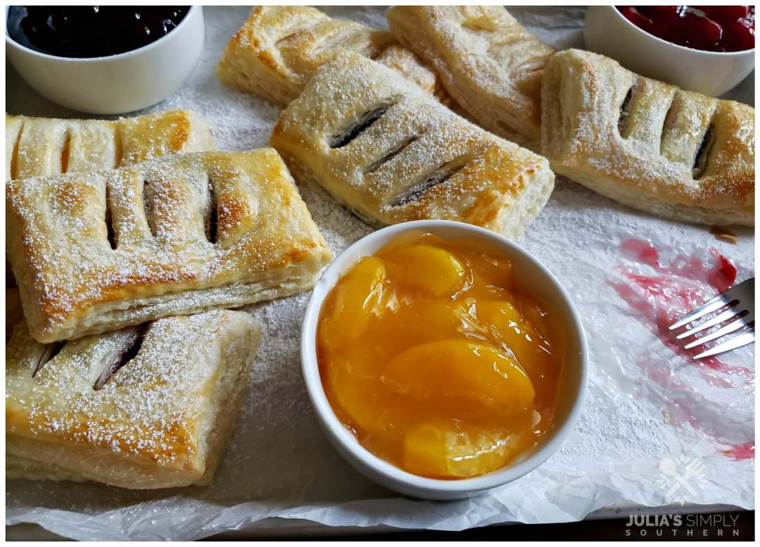 Assorted fruit hand pies on a confectioner's sugar coated sheet pan with extra fruit filling to be used for topping. Hand pies can be served alone or with a glazed topping or alongside a scoop of ice cream.