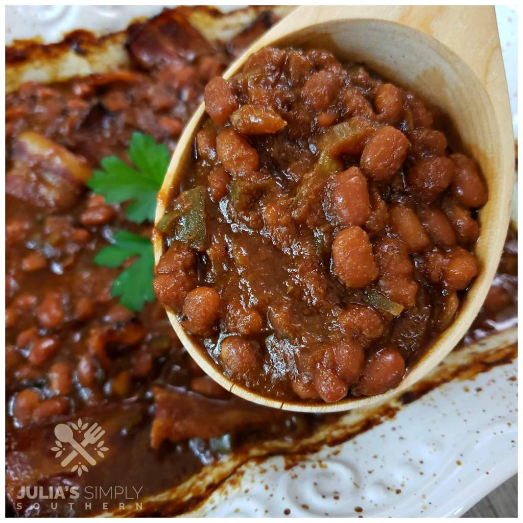 Homemade baked beans with bacon in a wooden serving spoon. Everyone loves this amazing side dish.