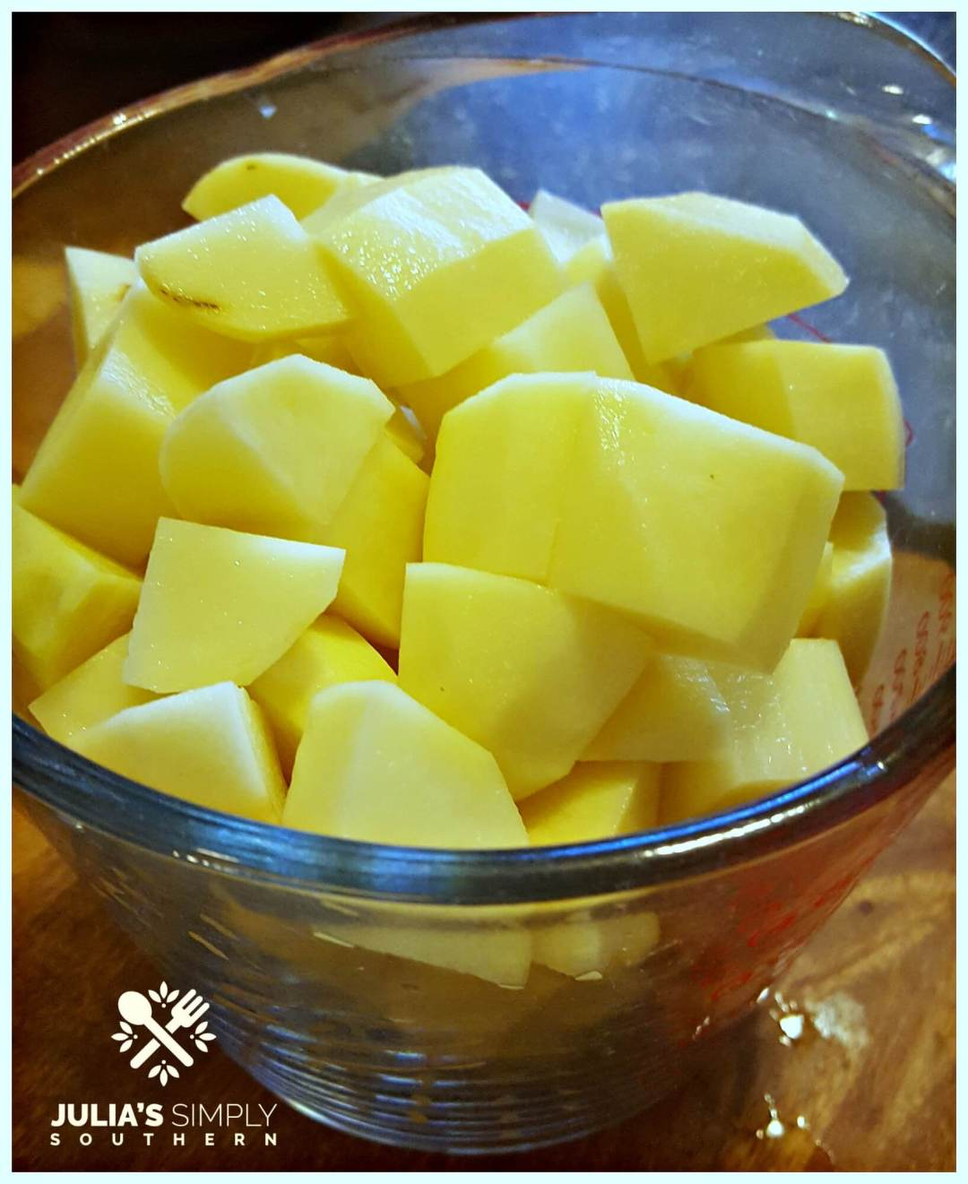 Raw cubes of Russet potato for a potato salad recipe in a large glass measuring cup