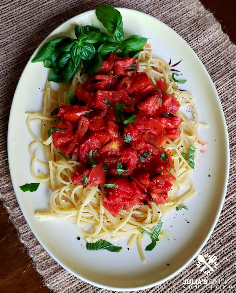 Yellow and white platter with an easy pasta meal with tomato and basil