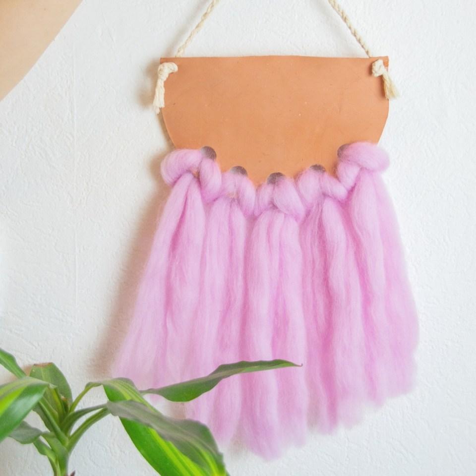 DIY Makramee Wanddeko in rosa aus Modellierfarbe und Filzwolle mit Buchtknoten hinter einer weißen wand