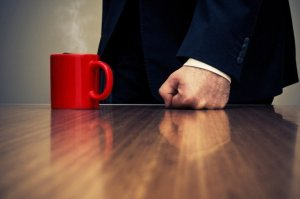 Businessman Hitting Desk with Fist Beside Coffee Cup