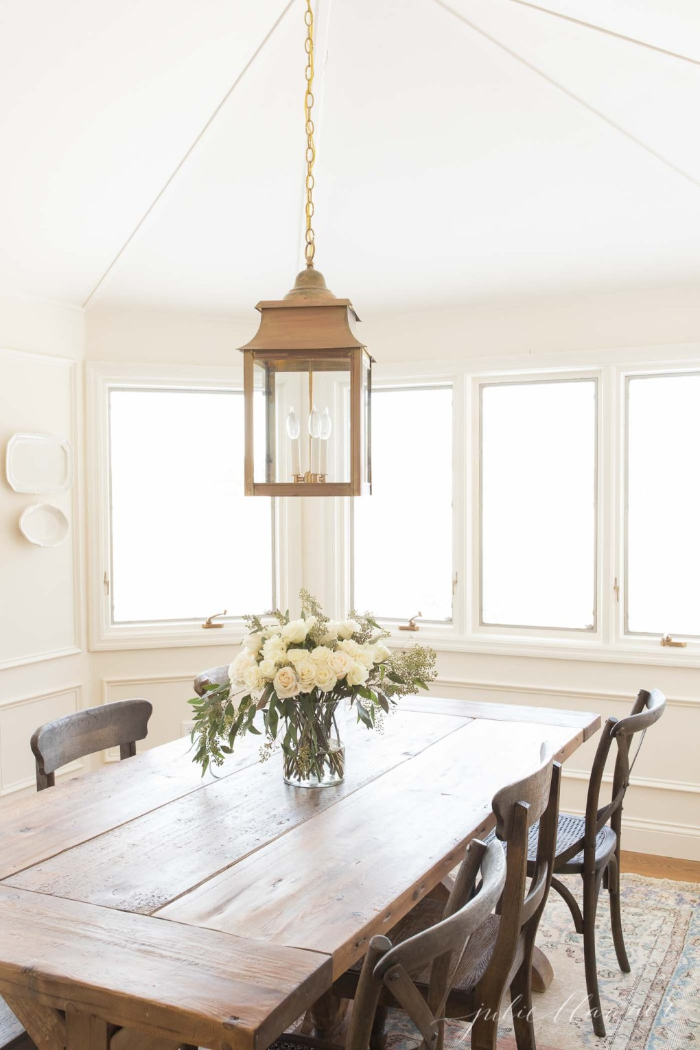 A white dining room with a farm table and a brass chandelier, white flowers on the table.