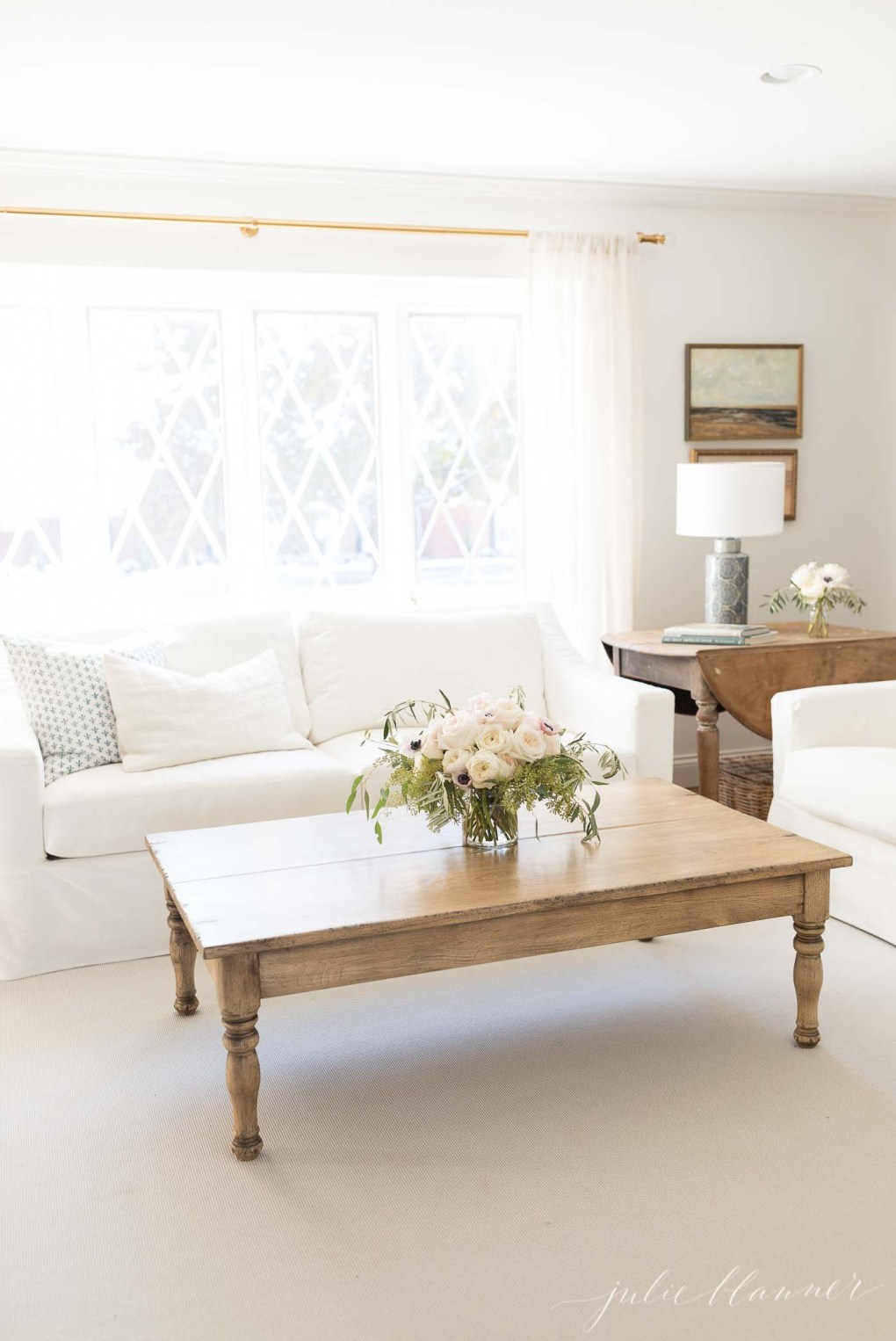 neutral living room with wood coffee table, white sofas