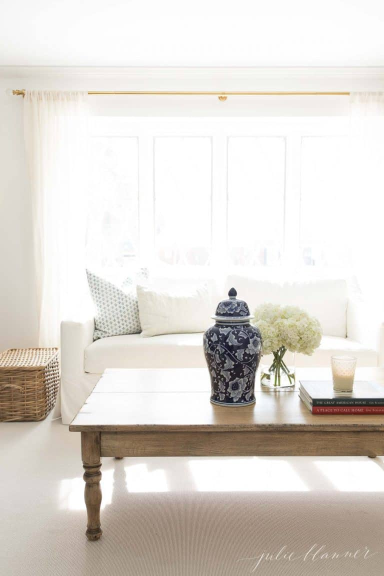 A neutral living room with a white sofa, wood coffee table and a pop of blue.