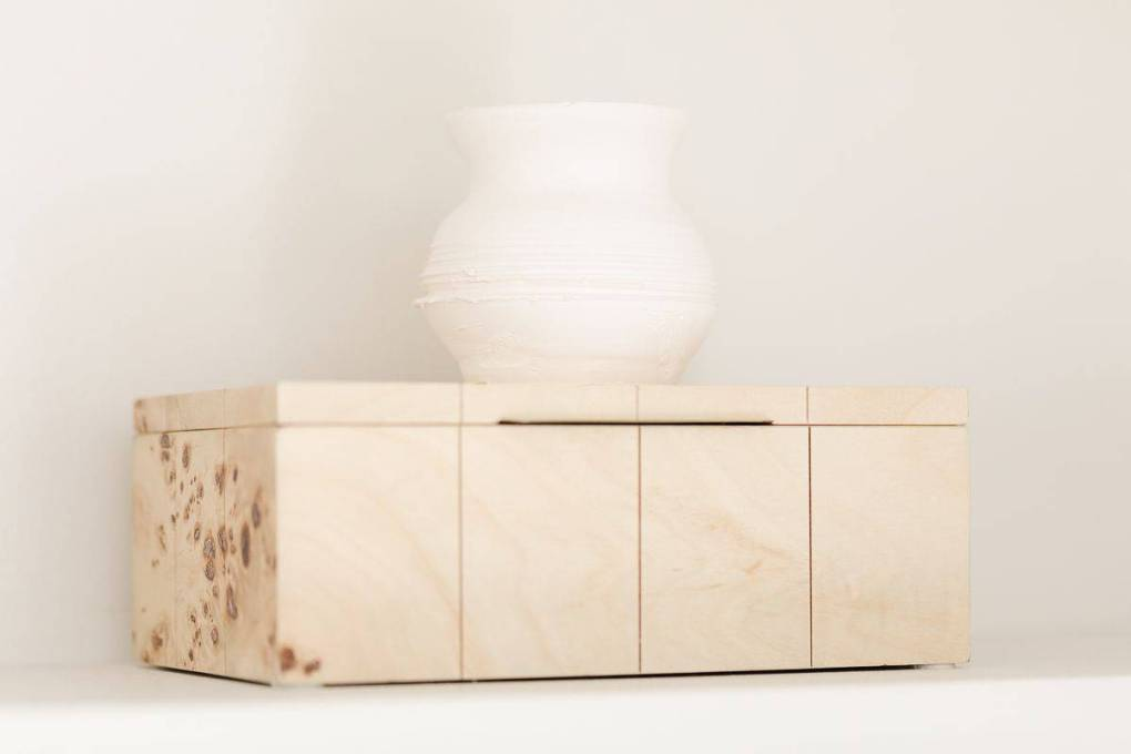 Bookshelf styling of a raw wood box with a small white vase on top.