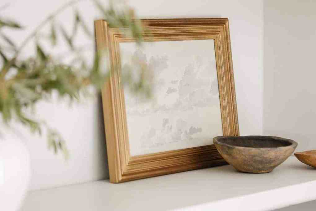 Bookshelf decor ideas of a gold framed piece of art and a small wood bowl in front, on white painted built ins.
