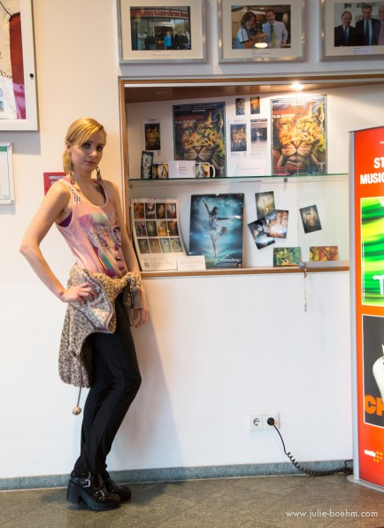 Julie Boehm in front of her exhibition promo: FARBWELTEN