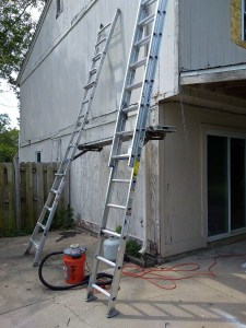 bee vacuum and ladders to remove bees from the side of a duplex