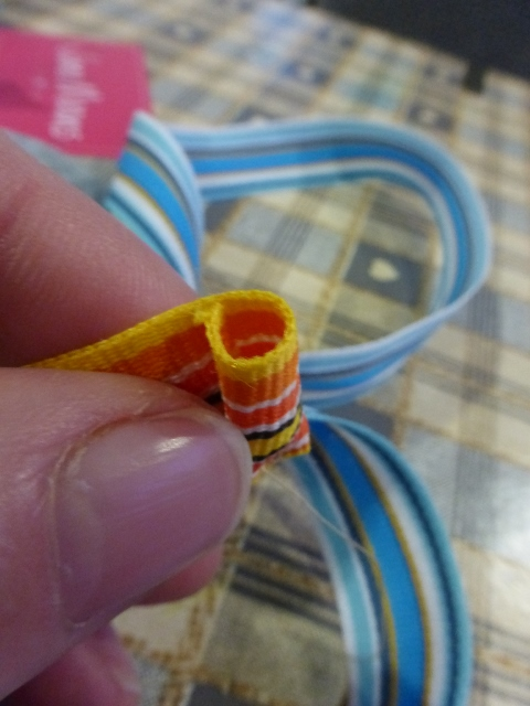 Roll the end of the yellow ribbon round to form a tiny cylinder and stitch to hold it in place