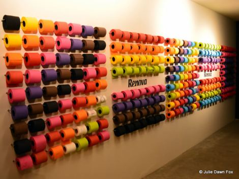 coloured toilet rolls on a wall