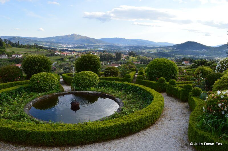 Ornamental pond and hedges with views over the Lima valley and mountains.