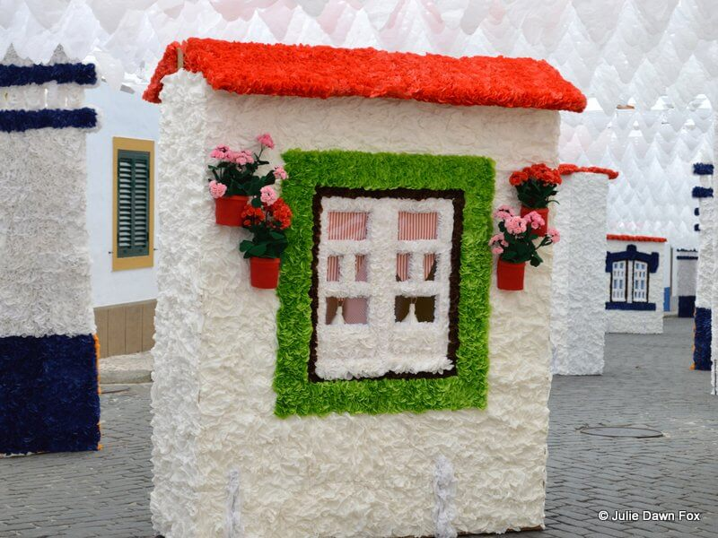 A tissue paper-covered board depicting a green-trimmed window with flower pots either side