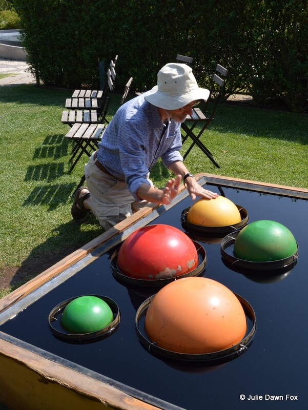 Man playing colourful circular drums in a pond.