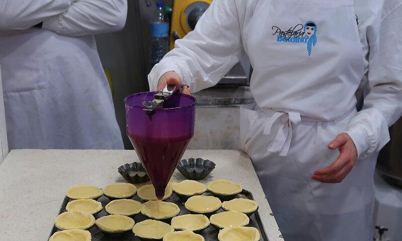 Filling cases with custard. Pastel de nata workshop, Pastelaria Batalha in Lisbon