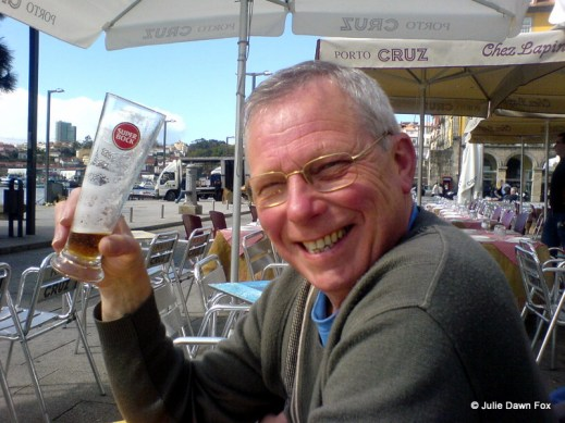 smiling man holds glass of beeer