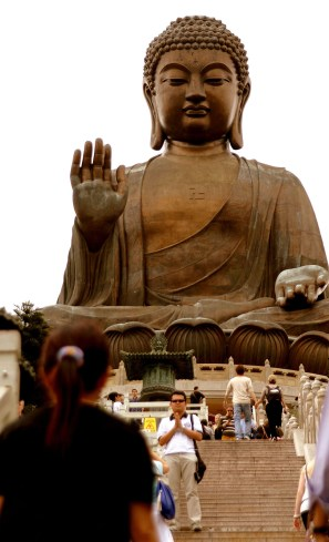 Tourists visiting The Big Buddha, with one man posing for a picture.