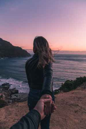 couple standing by the ocean at sunset