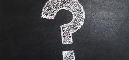 White, bold question mark made with chalk on a black chalkboard, questions
